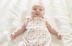 Bebê em uma cama de bebê Fotos de Stock