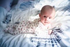Bebê em uma cama que olha a câmera Foto de Stock Royalty Free