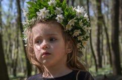 Bebê encantador com uma grinalda das flores brancas em sua cabeça ao andar na floresta em uma tarde ensolarada Fotografia de Stock