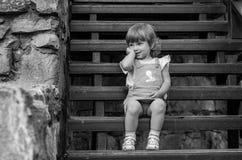 Bebê encantador da menina que senta-se nas escadas de madeira em um vestido bonito ao andar em Lviv foto de stock