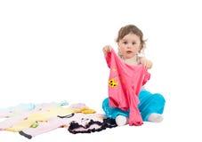 Bebê encantador que joga com a roupa, isolada no fundo branco foto de stock royalty free