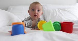 Bebê engraçado com os brinquedos na cama