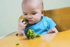 Bebê engraçado que come brócolis Imagens de Stock Royalty Free