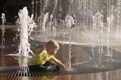 Bebê engraçado que espirra na fonte Criança bonito que joga com córrego da água fotografia de stock royalty free