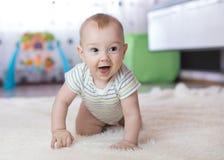 Bebê engraçado que rasteja no assoalho em casa Fotos de Stock