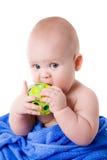 Bebê envolvido em uma esfera verde cortante de toalha azul Imagens de Stock Royalty Free