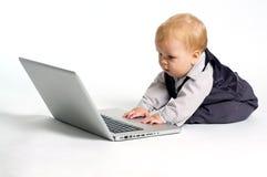 Bebê esperto com portátil Fotos de Stock
