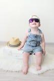 Bebê fashionably vestido bonito que senta-se na mala de viagem em casa Fotos de Stock