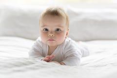 Bebê feliz bonito de 7 meses no tecido que encontra-se e que joga Fotos de Stock