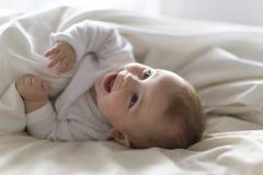 Bebê feliz bonito de 7 meses no tecido que encontra-se e que joga Foto de Stock Royalty Free