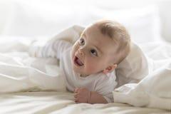 Bebê feliz bonito de 7 meses no tecido que encontra-se e que joga Imagem de Stock