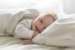 Bebê feliz bonito de 7 meses no tecido que encontra-se e que joga Foto de Stock