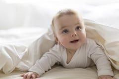 Bebê feliz bonito de 7 meses no tecido que encontra-se e que joga Imagens de Stock