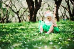 Bebê feliz bonito no passeio verde da saia do tutu exterior no jardim da mola imagem de stock royalty free