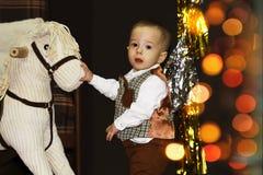 Bebê feliz bonito perto do cavalo de balanço em uma sala decorada do Natal com bokeh fotografia de stock