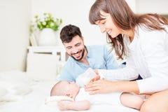 Bebê feliz da alimentação dos pais com leite foto de stock