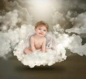 Bebê feliz do anjo que senta-se em nuvens Foto de Stock
