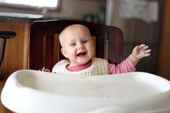 Bebê feliz do bebê de seis meses no babador que come na cadeira alta Fotos de Stock