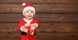 Bebê feliz em um traje Santa Claus do Natal com presentes Imagens de Stock