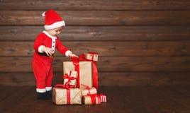 Bebê feliz em um traje Santa Claus do Natal com presentes Fotografia de Stock