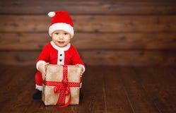 Bebê feliz em um traje Santa Claus do Natal com presentes Foto de Stock