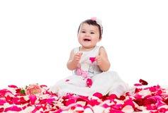 Bebê feliz entre as pétalas cor-de-rosa Imagens de Stock Royalty Free