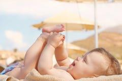 Bebê feliz na praia que encontra-se no vadio Fotos de Stock
