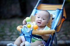 Bebê feliz no carrinho de criança que joga o brinquedo imagem de stock