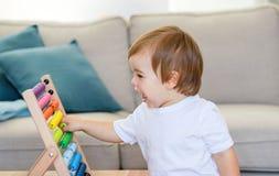 Bebê feliz pequeno bonito que joga com ábaco colorido Conceito adiantado da educação e do desenvolvimento imagem de stock royalty free