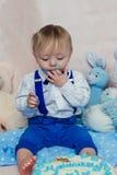 Bebê feliz que come o bolo para sua primeira festa de anos Fotos de Stock