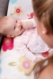 Bebê feliz que encontra-se no sorriso traseiro na mãe Imagem de Stock