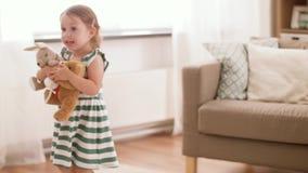 Bebê feliz que joga com brinquedos macios em casa video estoque