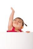 Bebê feliz que prende a placa branca e que alcanga acima Imagem de Stock Royalty Free