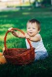 Bebê feliz que sorri e que joga com cesta e riso Fotografia de Stock Royalty Free