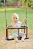 Bebê feliz que tem o divertimento em um passeio do balanço em um campo de jogos Fotos de Stock Royalty Free