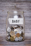 Bebê, frasco do dinheiro com as moedas na tabela de madeira imagem de stock