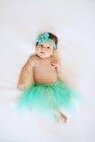 Bebê idoso de dois meses que encontra-se para baixo vestindo uma saia e uma curva em seu cabelo Imagens de Stock