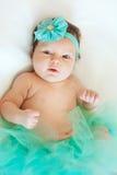Bebê idoso de dois meses que encontra-se para baixo vestindo uma saia e uma curva em seu cabelo Fotos de Stock