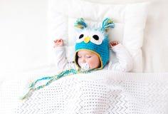 Bebê idoso de sete meses que dorme na cama Foto de Stock
