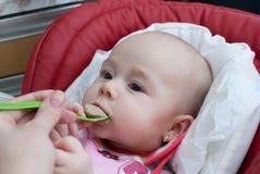 Bebê infantil na cadeira das crianças que come a refeição Imagens de Stock Royalty Free