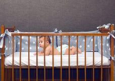 Bebê infantil que coloca no berço decorado foto de stock