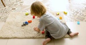 Bebê irreconhecível que joga com tijolos do brinquedo video estoque