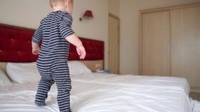Bebê loiro bonito pula alegremente na cama grande em um quarto de hotel em câmera lenta vídeos de arquivo
