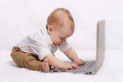 Bebê louro bonito que trabalha com portátil foto de stock royalty free