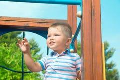 Bebê louro caucasiano bonito com a criança dos olhos azuis de 2 anos de suportes velhos no campo de jogos no sorriso do parque da Fotografia de Stock
