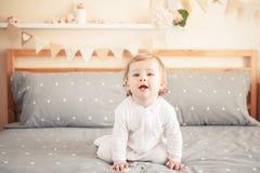 Bebê louro caucasiano no onesie branco que senta-se na cama no quarto Foto de Stock Royalty Free