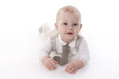 Bebê-menino de sorriso em um rastejamento do terno do romper Fotos de Stock Royalty Free