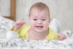 Bebê 6-7 meses de encontro de grito em seu estômago Um bebê caucasiano no amarelo é de grito e mostrando 2 dentes de bebê, saindo fotografia de stock royalty free