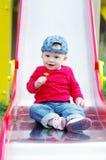 Bebê na corrediça com dente-de-leão à disposição Fotos de Stock Royalty Free