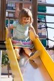 Bebê   na corrediça na área do campo de jogos Fotos de Stock